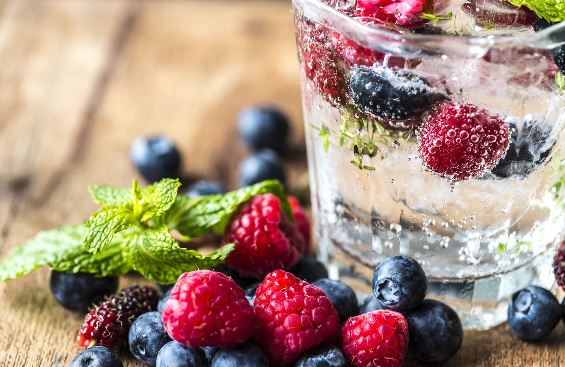 Water glass with fresh berries and mint