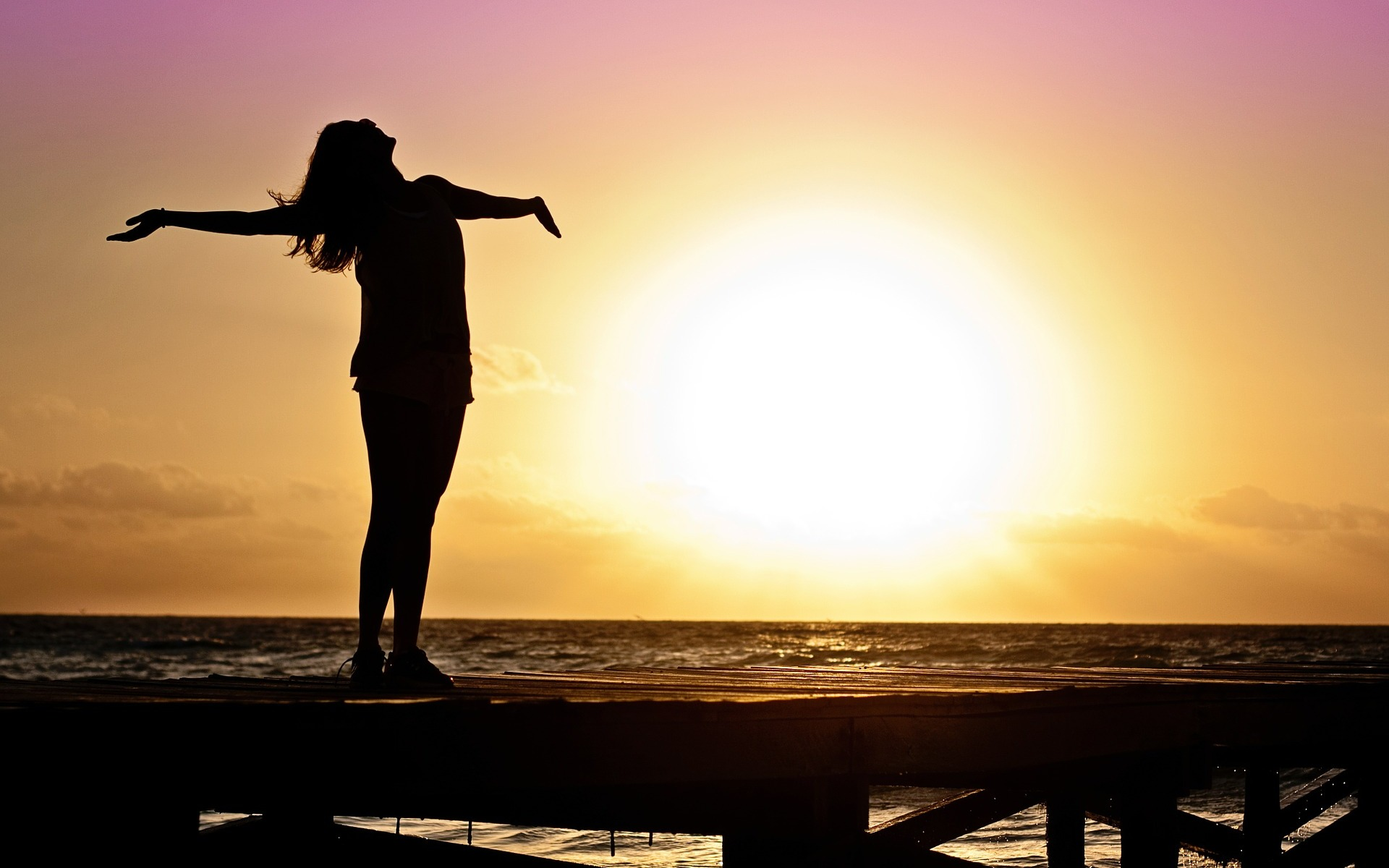 photo of woman stretching with sunrise