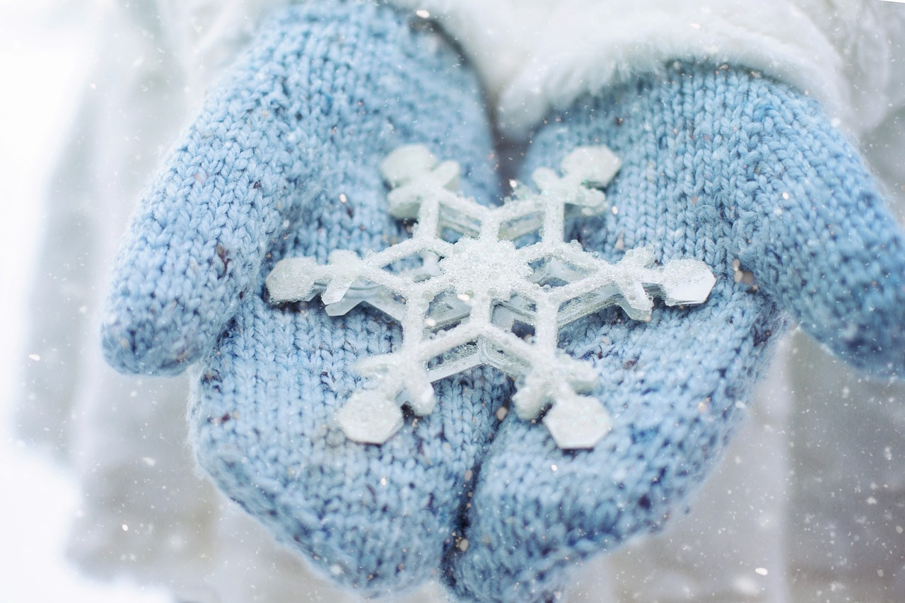 person wearing blue mittens and holding large white snowflake ornament