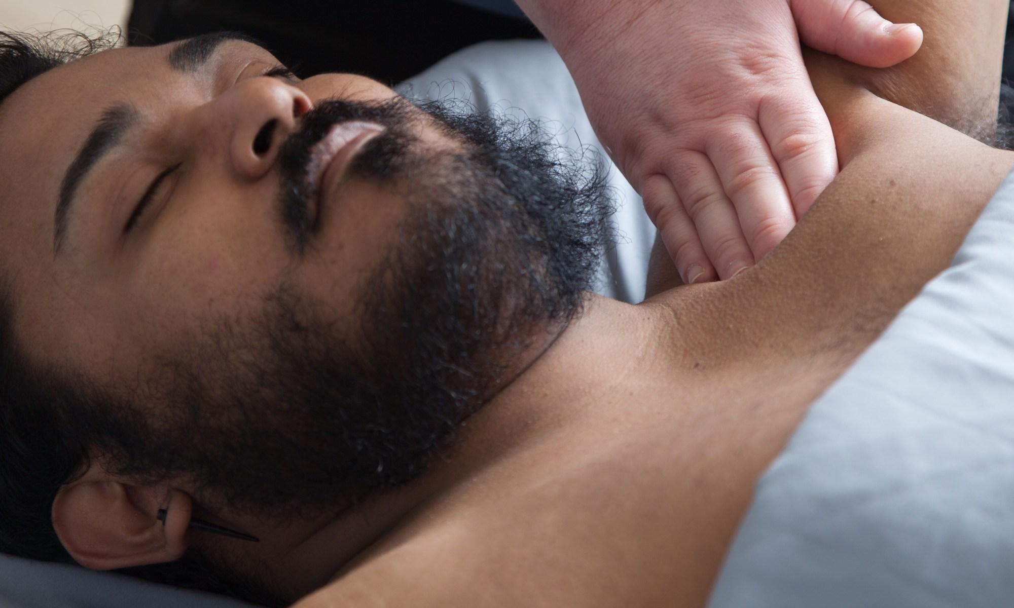 massage therapist working on male client shoulder