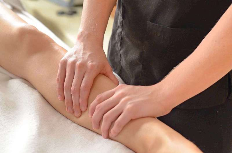 Therapist performing massage on client's lower left leg on table